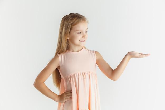 Stylowa mała uśmiechnięta dziewczyna pozuje w sukience na białym tle na tle białego studia. kaukaski blond modelka. ludzkie emocje, wyraz twarzy, dzieciństwo. pokazywanie na pustej spacji.