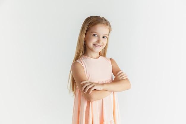 Stylowa mała uśmiechnięta dziewczyna pozuje w sukience na białym tle na tle białego studia. kaukaski blond modelka. ludzkie emocje, wyraz twarzy, dzieciństwo. stojąc z rękami skrzyżowanymi.