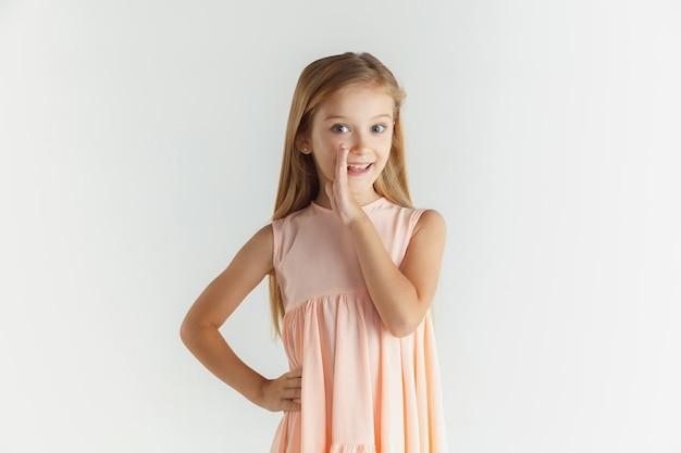 Stylowa mała uśmiechnięta dziewczyna pozuje w sukience na białym tle na tle białego studia. kaukaski blond modelka. ludzkie emocje, wyraz twarzy, dzieciństwo. szepcząc sekret, uśmiechając się.