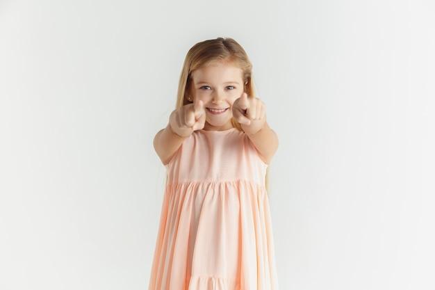 Stylowa mała uśmiechnięta dziewczyna pozuje w sukience na białym tle na tle białego studia. kaukaski blond modelka. ludzkie emocje, wyraz twarzy, dzieciństwo. wskazując na aparat, wybierając.