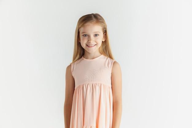 Stylowa mała uśmiechnięta dziewczyna pozuje w sukience na białym tle na tle białego studia. kaukaski blond modelka. ludzkie emocje, wyraz twarzy, dzieciństwo. wygląda spokojnie, stojąc, patrząc w kamerę.