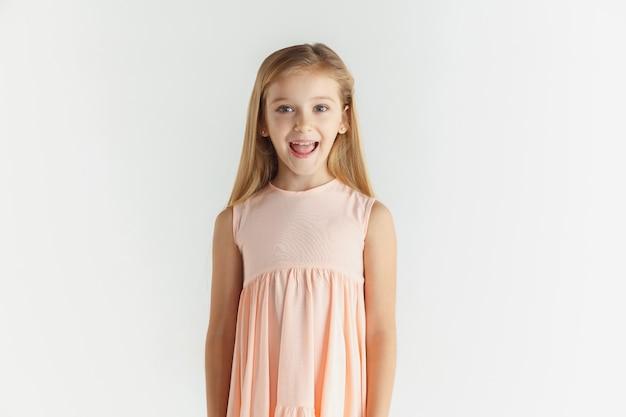 Stylowa mała uśmiechnięta dziewczyna pozuje w sukience na białym tle na tle białego studia. kaukaski blond modelka. ludzkie emocje, wyraz twarzy, dzieciństwo. zastanawiał się, patrząc w kamerę.