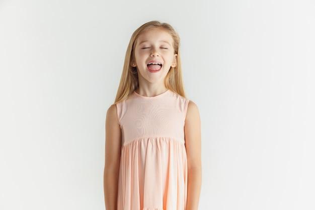 Stylowa mała uśmiechnięta dziewczyna pozuje w sukience na białym tle na tle białego studia. kaukaski modelka. ludzkie emocje, wyraz twarzy, dzieciństwo. śmiejąc się z zamkniętymi oczami.