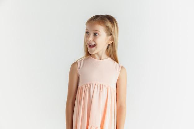 Stylowa mała uśmiechnięta dziewczyna pozuje w sukience na białym tle na tle białego studia. kaukaski modelka. ludzkie emocje, wyraz twarzy, dzieciństwo. zdziwiony, zdumiony, zszokowany. patrząc z boku.