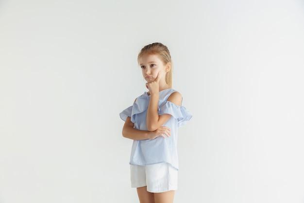 Stylowa mała uśmiechnięta dziewczyna pozuje w ubranie na białym tle. kaukaski blond modelka. ludzkie emocje, wyraz twarzy, dzieciństwo. rozważny. myślenie, wybieranie.