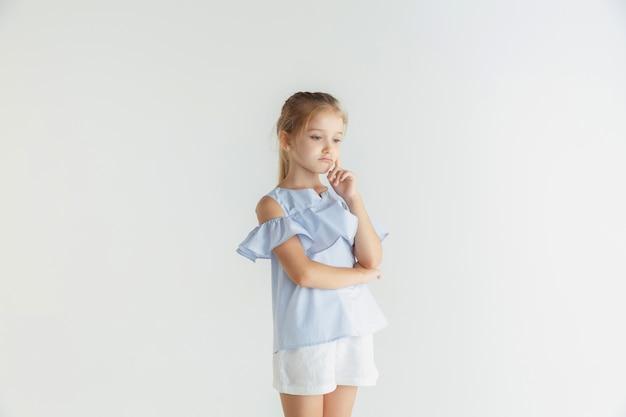 Stylowa mała uśmiechnięta dziewczyna pozuje w ubranie na białym tle. kaukaski blond modelka. ludzkie emocje, wyraz twarzy, dzieciństwo. rozważny
