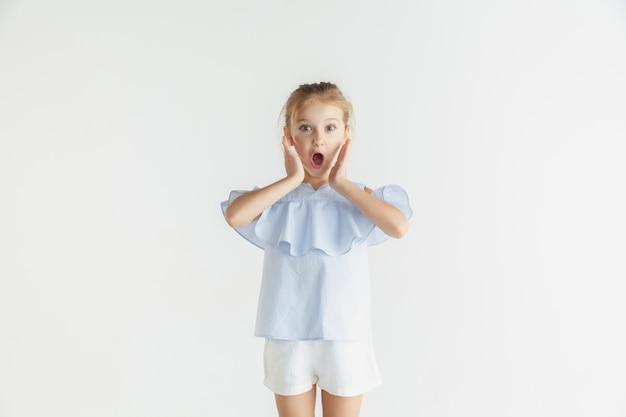 Stylowa mała uśmiechnięta dziewczyna pozuje w ubranie na białym tle. kaukaski blond modelka. ludzkie emocje, wyraz twarzy, dzieciństwo, sprzedaż