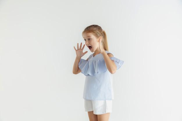 Stylowa mała uśmiechnięta dziewczyna pozuje w ubranie na białym tle. kaukaski blond modelka. ludzkie emocje, wyraz twarzy, dzieciństwo. zszokowany, zdumiony.
