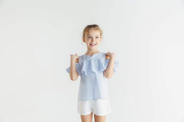 Stylowa mała uśmiechnięta dziewczyna pozuje w ubranie na białym tle na białej ścianie. kaukaski blond modelka. ludzkie emocje, wyraz twarzy, dzieciństwo. pokazywanie, zapraszanie lub powitanie.