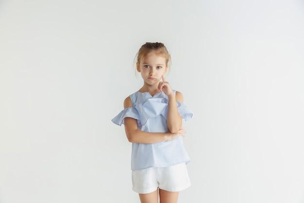 Stylowa mała uśmiechnięta dziewczyna pozuje w ubranie na białym tle na białej ścianie. kaukaski blond modelka. ludzkie emocje, wyraz twarzy, dzieciństwo. rozważny. myślenie, wybieranie.