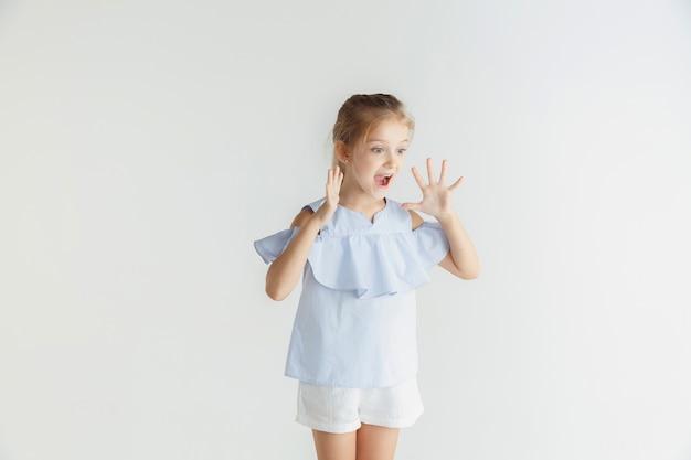 Stylowa mała uśmiechnięta dziewczyna pozuje w ubranie na białym tle na białej ścianie. kaukaski blond modelka. ludzkie emocje, wyraz twarzy, dzieciństwo, sprzedaż. zszokowany, zdumiony.