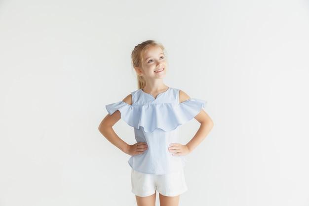 Stylowa mała uśmiechnięta dziewczyna pozuje w ubranie na białym tle na białej ścianie. kaukaski blond modelka. ludzkie emocje, wyraz twarzy, dzieciństwo. uśmiechnięty, trzymając się za ręce na biodrach.
