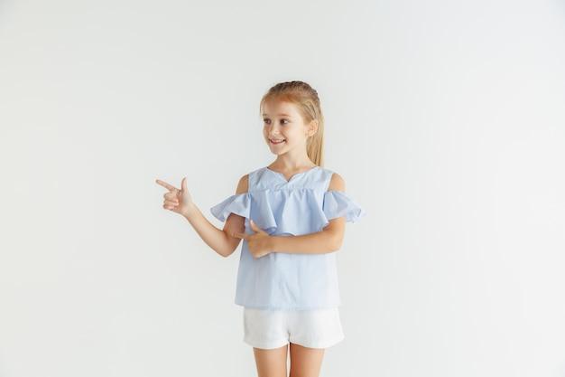 Stylowa mała uśmiechnięta dziewczyna pozuje w ubranie na białym tle na białej ścianie. kaukaski blond modelka. ludzkie emocje, wyraz twarzy, dzieciństwo. wskazując na pustą spację.