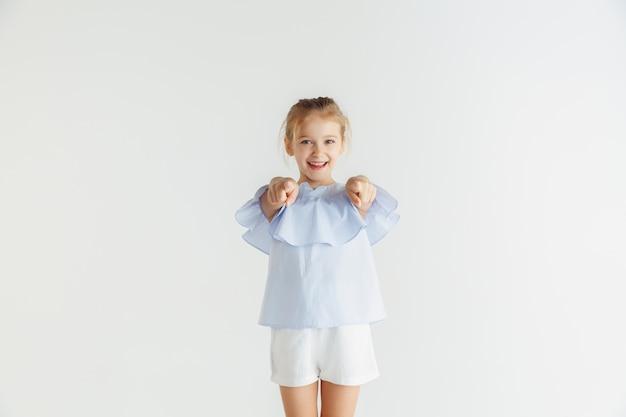 Stylowa mała uśmiechnięta dziewczyna pozuje w ubranie na białym tle na białej ścianie. kaukaski blond modelka. ludzkie emocje, wyraz twarzy, dzieciństwo. wskazując, wybierając, uśmiechając się.