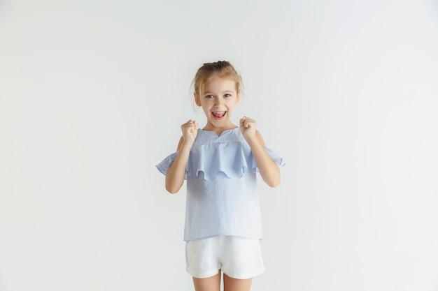 Stylowa mała uśmiechnięta dziewczyna pozuje w ubranie na białym tle na białej ścianie. kaukaski blond modelka. ludzkie emocje, wyraz twarzy, dzieciństwo. zwycięstwo, świętowanie, uśmiech.