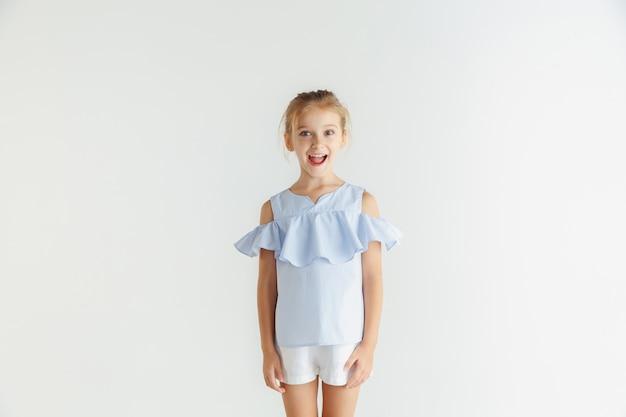 Stylowa mała uśmiechnięta dziewczyna pozuje w ubranie na białym tle na białej ścianie. kaukaski blond modelka. ludzkie emocje, wyraz twarzy, dzieciństwo.