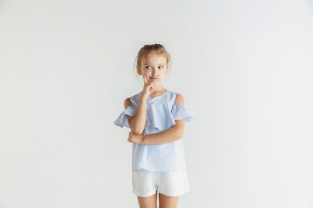Stylowa mała uśmiechnięta dziewczyna pozuje w ubranie na białym tle na białym studio