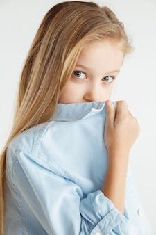 Stylowa mała uśmiechnięta dziewczyna pozuje w ubranie na białym tle na ścianie białego studia