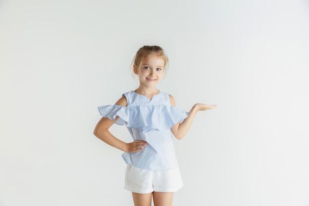 Stylowa mała uśmiechnięta dziewczyna pozuje w ubranie na białym tle na tle białego studia. kaukaski blond modelka. ludzkie emocje, wyraz twarzy, dzieciństwo. pokazuje pustą przestrzeń, zaprasza