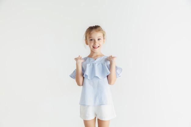 Stylowa mała uśmiechnięta dziewczyna pozuje w ubranie na białym tle na tle białego studia. kaukaski blond modelka. ludzkie emocje, wyraz twarzy, dzieciństwo. pokazywanie, zapraszanie lub powitanie.