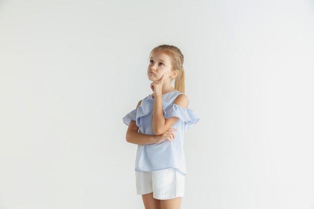 Stylowa mała uśmiechnięta dziewczyna pozuje w ubranie na białym tle na tle białego studia. kaukaski blond modelka. ludzkie emocje, wyraz twarzy, dzieciństwo. rozważny. myślenie, wybieranie.