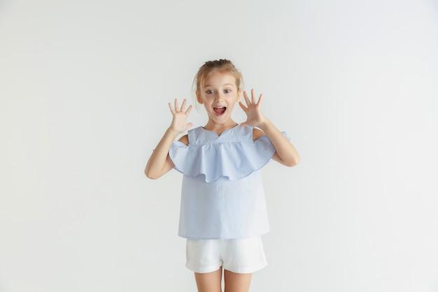 Stylowa mała uśmiechnięta dziewczyna pozuje w ubranie na białym tle na tle białego studia. kaukaski blond modelka. ludzkie emocje, wyraz twarzy, dzieciństwo, sprzedaż. zszokowany, zdumiony.