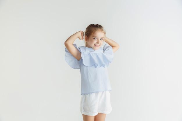 Stylowa mała uśmiechnięta dziewczyna pozuje w ubranie na białym tle na tle białego studia. kaukaski blond modelka. ludzkie emocje, wyraz twarzy, dzieciństwo. zwycięstwo, świętowanie, uśmiech.