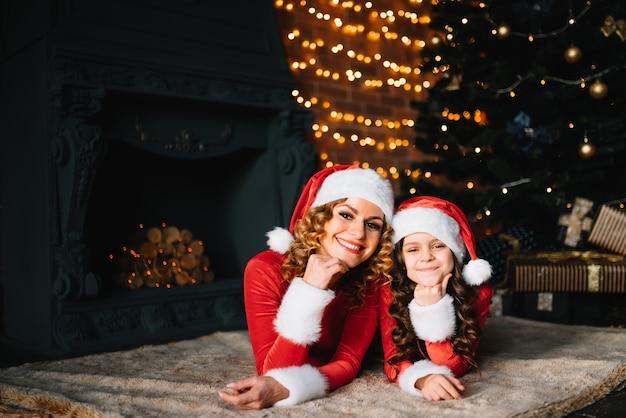 Stylowa mama z małą córeczką w strojach bożonarodzeniowych w pobliżu choinki. wesołych świąt.