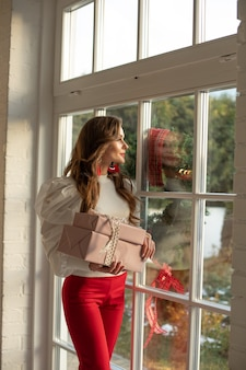 Stylowa marzycielska młoda kobieta trzyma zapakowane prezenty
