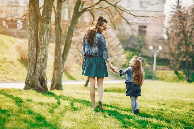 Stylowa matka z długimi włosami i dżinsową kurtką bawiącą się ze swoją małą uroczą córeczką