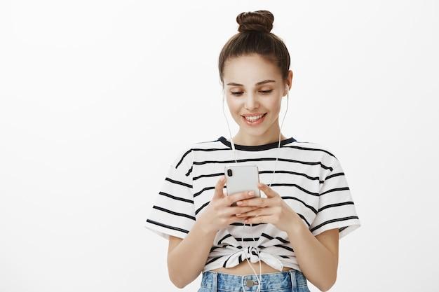 Stylowa miejska dziewczyna w słuchawkach, uśmiechnięta i zadowolona patrząc na wyświetlacz smartfona