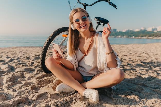 Stylowa młoda atrakcyjna blond uśmiechnięta kobieta siedzi na plaży z rowerem w słuchawkach, słuchając muzyki