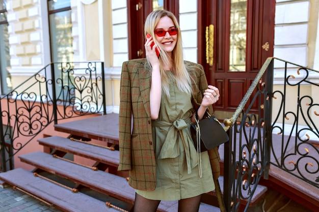 Stylowa młoda blondynka biznesu rozmawiająca przez telefon i pozująca na ulicy w paryżu, modny stylowy kobiecy strój folwarczny, kurtka oversize, ciepłe kolory.