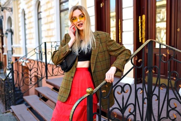 Stylowa młoda blondynka pozuje w pobliżu luksusowego sklepu i mówi przy swoim smartfonie, modnym nowoczesnym stroju, obszernej kurtce i saszetce.