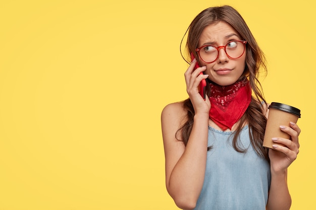 Stylowa młoda brunetka w okularach, pozowanie na żółtej ścianie