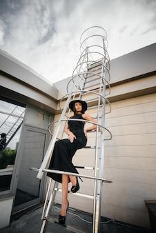 Stylowa młoda dziewczyna pozuje w kapeluszu na pożarowej ucieczce centrum biznesu. moda