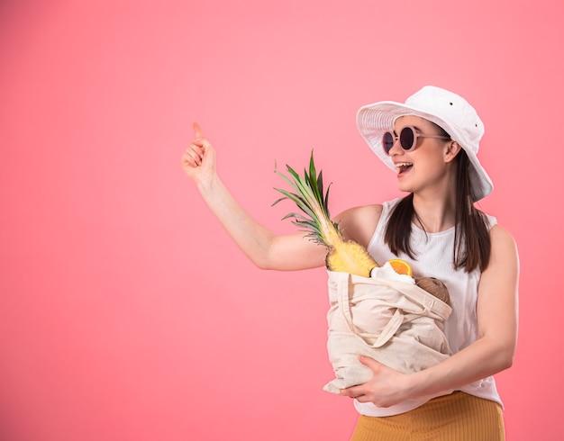 Stylowa młoda dziewczyna w białym kapeluszu i okularach przeciwsłonecznych, uśmiecha się i trzyma eko torbę z egzotycznymi owocami