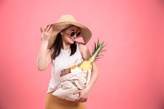 Stylowa młoda dziewczyna w dużym kapeluszu i okularach przeciwsłonecznych uśmiecha się i trzyma eko torbę z egzotycznymi owocami na różowym tle.
