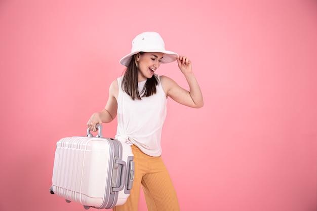 Stylowa młoda dziewczyna w kapeluszu z walizką. letnie wakacje i podróże