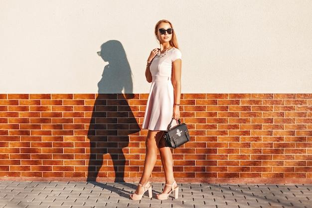 Stylowa młoda dziewczyna w okularach przeciwsłonecznych w różowej spódnicy z czarną torbą w pobliżu ściany z cegły.