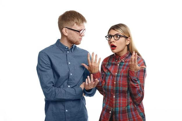 Stylowa młoda europejska para w okularach kłócąca się: emocjonalna blondynka ze zmęczonym wyglądem, zmęczona i zestresowana, wyjaśniając swojemu zrzędliwemu brodatemu mężowi, że ma rację