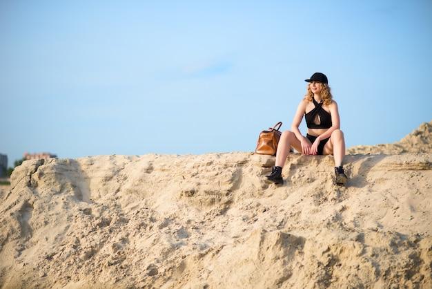 Stylowa młoda i piękna kobieta w czarnej bieliźnie w czapce i skórzanych butach ze skórzaną torbą siedzi na piaszczystym kamieniołomie w słoneczny ciepły letni dzień.