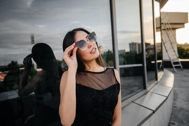 Stylowa młoda i seksowna dziewczyna pozuje przed centrum biznesu w czerni. moda i styl