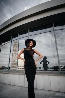 Stylowa młoda i seksowna dziewczyna pozuje przed centrum biznesu w czerni. modny styl.
