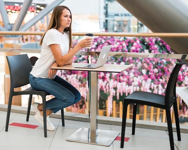 Stylowa młoda kobieta, ciesząc się kawą