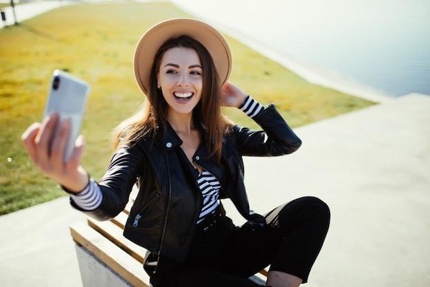 Stylowa młoda kobieta dziewczyna robi selfie w parku w pobliżu jeziora miejskiego w zimny, słoneczny letni dzień, ubrana w czarne ubrania
