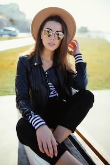 Stylowa młoda kobieta dziewczyna siedzi w parku w pobliżu jeziora miejskiego w zimny słoneczny letni dzień, ubrana w czarne ubrania