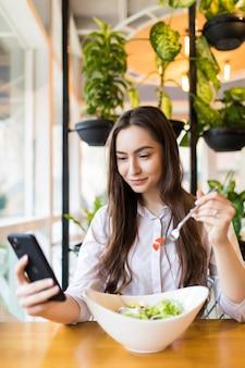 Stylowa młoda kobieta je zdrową sałatkę na tarasie restauracji, czując się szczęśliwa w letni dzień