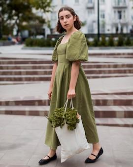 Stylowa młoda kobieta niosąc torbę na zakupy