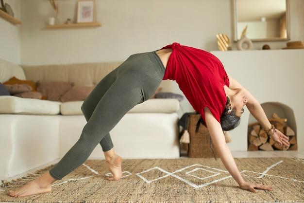 Stylowa młoda kobieta o pięknym, elastycznym ciele praktykująca jogę vinyasa flow, wykonująca mostek lub urdhva dhanurasana, rozciągająca przód tułowia podczas ćwiczeń zginania do tyłu, pozująca w przytulnym salonie